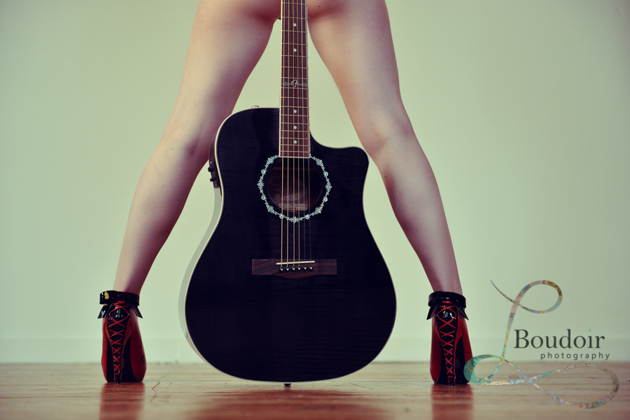boudoir photo of guitar between a women's legs